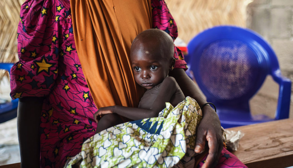 This photo taken on June 30, 2016 shows a young girl suffering from severe acute malnutrition sitting on her mother's lap, at one of the Unicef nutrition clinics, in the Muna informal settlement, which houses nearly 16,000 IDPs (internally displaced people) in the outskirts of Maiduguri capital of Borno State, northeastern Nigeria.    Nigeria has pledged to do more to tackle food shortages among people made homeless by Boko Haram, as the United Nations warned some 50,000 children could starve to death this year in one northeastern state alone. / AFP / STEFAN HEUNIS        (Photo credit should read STEFAN HEUNIS/AFP/Getty Images)