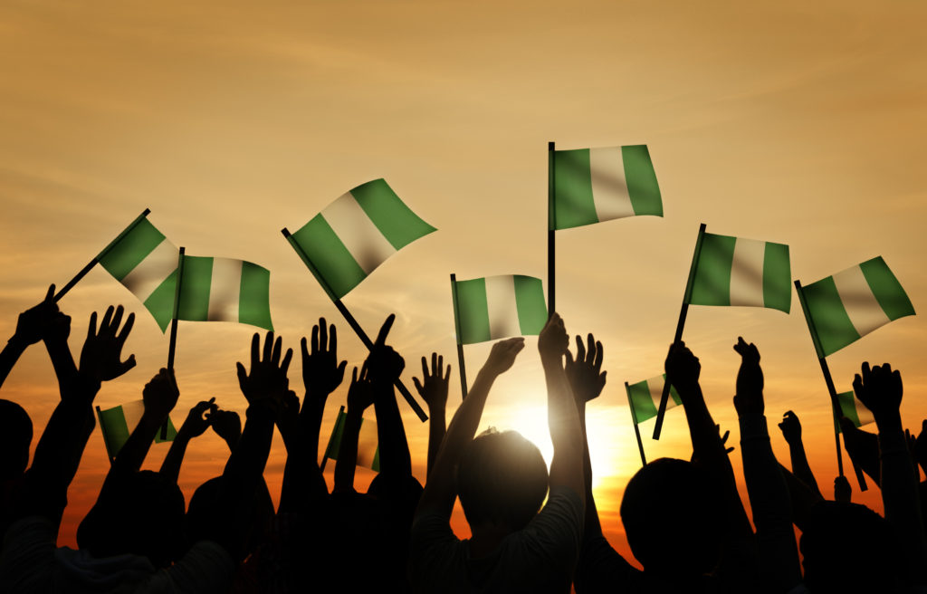 Group of People Waving Flag of Nigeria in Back Lit