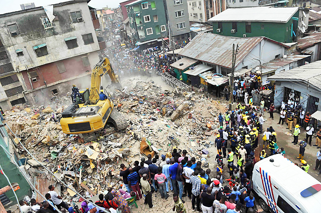 A crowd looks on as a rescue worker operates a bulldozer in the search for bodies in the rubble of a collapsed building in Lagos on July 26, 2017, after the collapse of the four-story building in the city.  Eight people have been confirmed dead by officials of Lagos State Emergency Management Agency (LASEMA) and fifteen rescued alive, while operators were escavating debris to rescue many that are trapped as a four-story building collapsed in the Nigerian financial capital.   / AFP PHOTO / PIUS UTOMI EKPEI